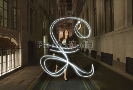 businesswoman light painting glowing pound sign