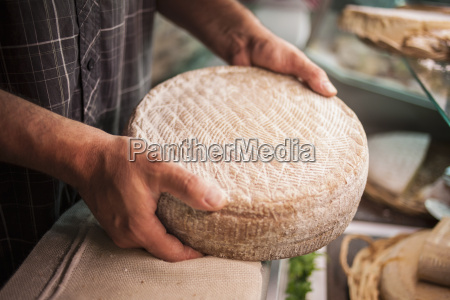 mature man holding cheese close up