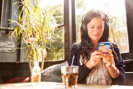 mid adult woman wearing earphones using