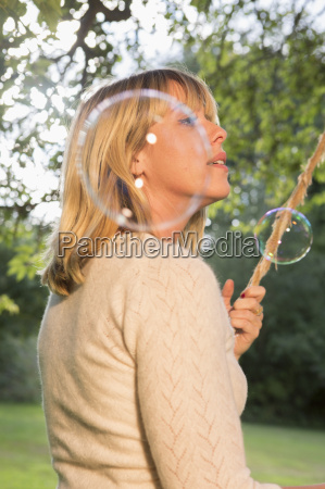 woman on swing blowing soap bubbles