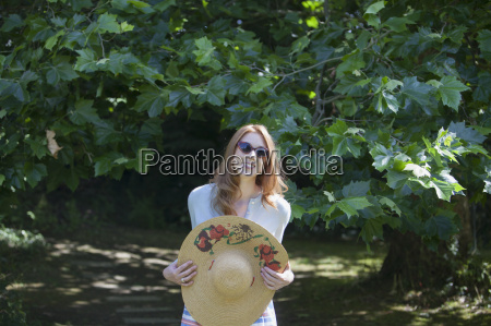 woman holding large straw hat in