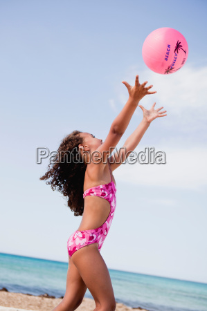 young girl at beach playing ball