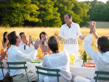 group of people having dinner sunset