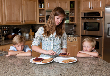teenage girl preparing sandwiches for brothers