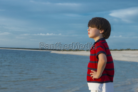 young boy standing in sea hands