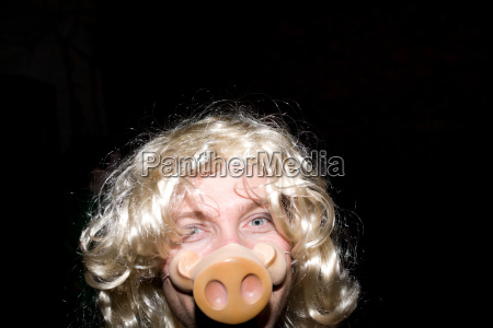 man wearing blonde wig and pigs
