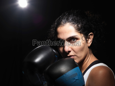 portrait of female boxer against black
