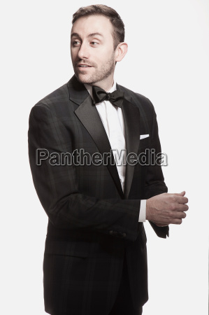 man in tuxedo standing against white