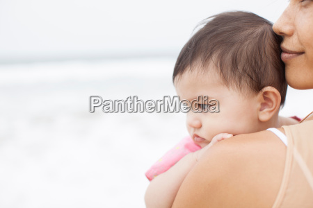 baby girl in mothers arms looking
