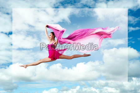 ballerina leaping against cloudy sky