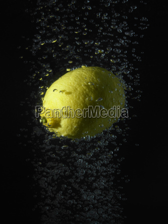 lemon in bubbles black background
