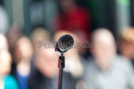microphone in focus blurred audience in