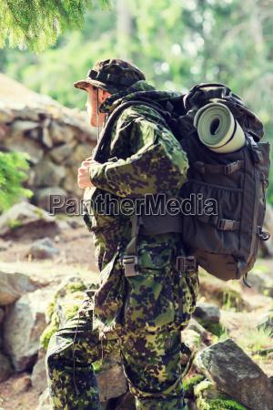 giovane soldato con zaino in foresta