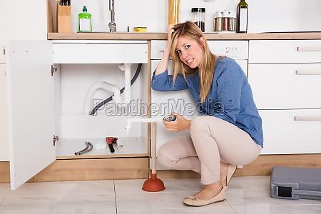 frustrato donna avendo cucina lavello problema