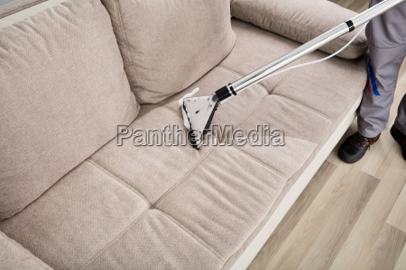 person cleaning sofa with vacuum cleaner