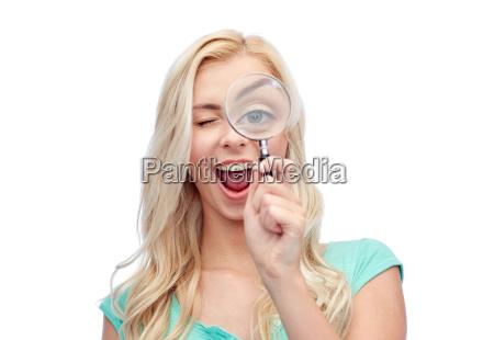 felice giovane donna con lente dingrandimento