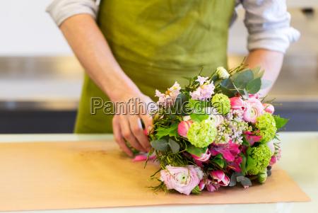 fiorista che avvolge i fiori in