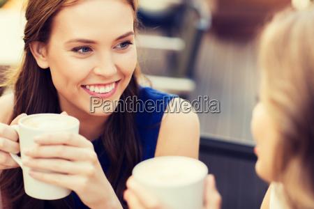 sorridente giovani donne con tazze di