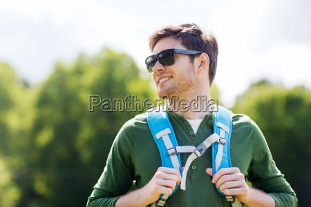 felice giovane uomo con zaino escursioni