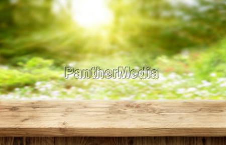 wooden desk on sunny bokeh background
