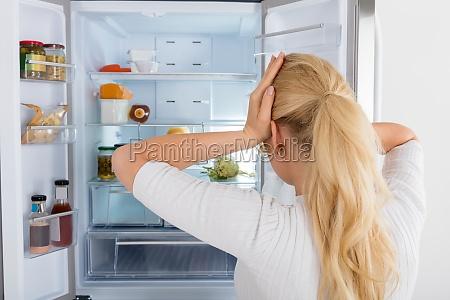 donna che osserva allinterno del frigo