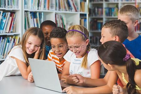 sorridenti ragazzi della scuola guardando laptop