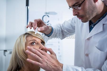 optometrista mettere gocce negli occhi dei