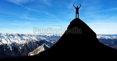 uomo in piedi sulla cima della