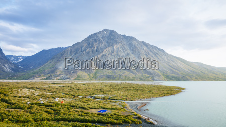a hikers tent camp beside turquoise