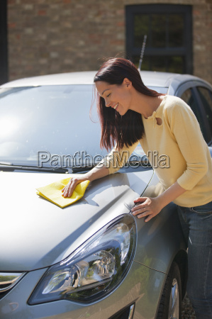 woman washing and wiping car with