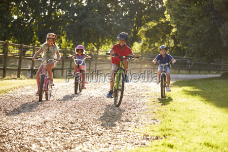 quattro bambini in bicicletta in campagna