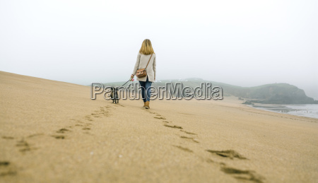 woman walking with dog on the