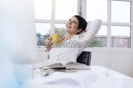 donna sorridente che tiene una tazza
