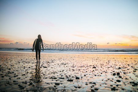 young woman with surfboard walking on