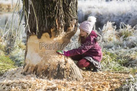 girl touching tree trunk in winter