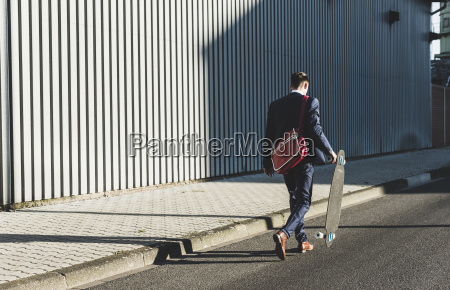 young businessman walking with skateboard on