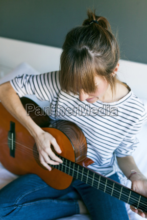 young woman playing guitar sitting on