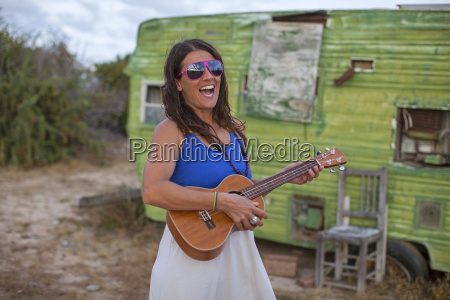 adult woman playing her ukulele in