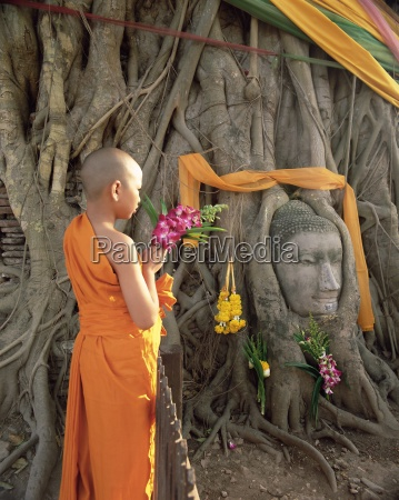 novice monk with offering of flowers