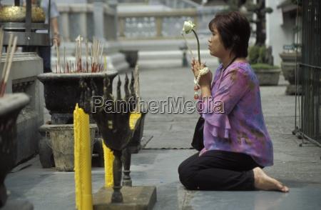 thai buddhist woman praying at temple