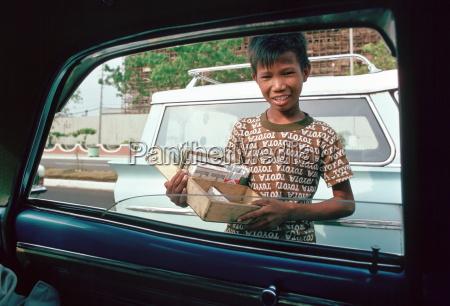 ragazzo vende sigarette ai finestrini dellauto