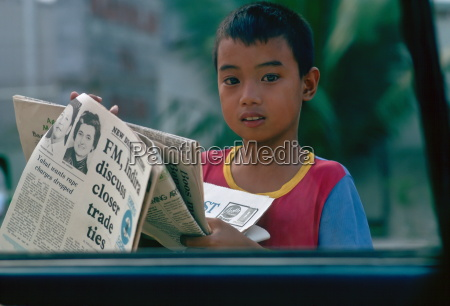boy vende giornali ai finestrini delle