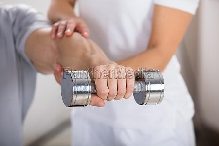 fisioterapista che aiuta luomo a esercitare
