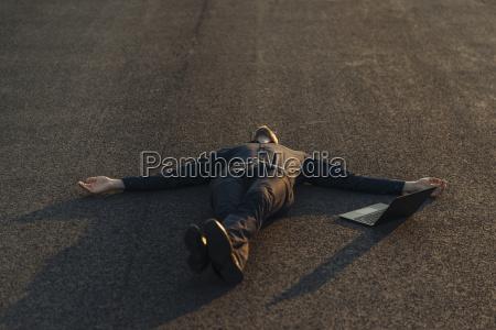 businessman lying on a road next