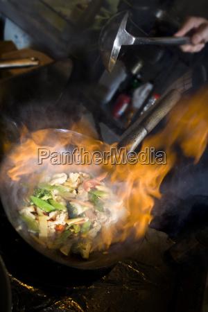 cucinare con wok in fiamme
