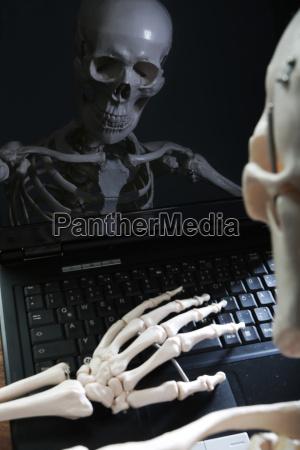 scheletro riflettendo nel monitor del computer