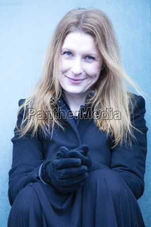 portrait of smiling woman wearing gloves