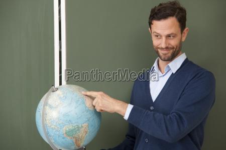 insegnante che punta al globo in