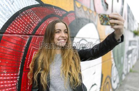 usmiechnieta nastoletnia dziewczyna bierze selfie przy