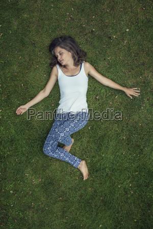 donna sdraiata su un prato con